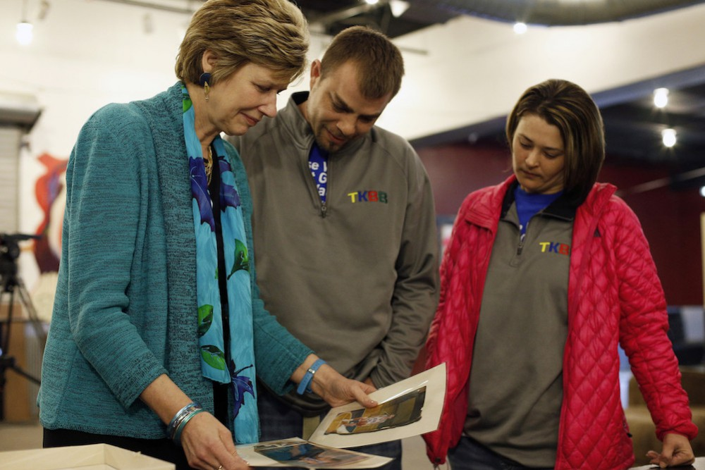 University of Delaware Professor Debra Hess Norris, left, shows Ricky and Traci Harris some of the more than 300 family photographs that were cleaned, repaired and salvage by her students, during a press conference at The Warehouse Youth Center in Washington Court House, Ohio on Friday, March 13, 2015.  Ricky's three children and his mother all died in a house fire the morning after Christmas, and the photos were about the only items salvaged from the blaze.  (AP Photo/The Columbus Dispatch, Kyle Robertson)